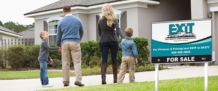 Family in front of home for sale and Exit Smart Sign